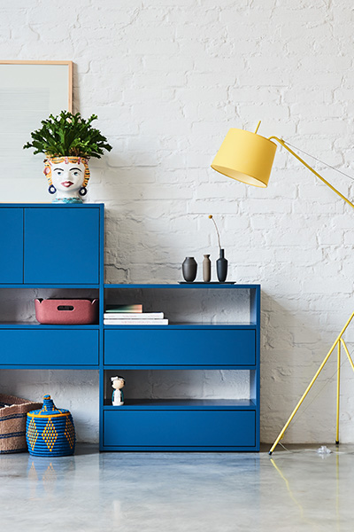 Blue sideboard divided on two levels with large drawers, two small doors and three open shelves