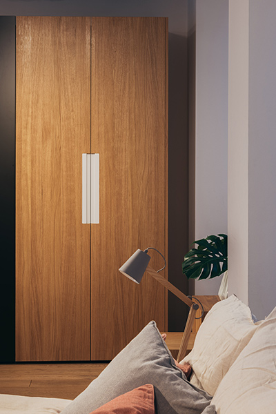 Wardrobe with four black and two oak swing doors and four handles in white and two in oak