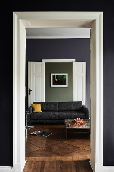 Living room with sofa in lava-black structured fabric and coffee table with tabletop in brown emperador marble