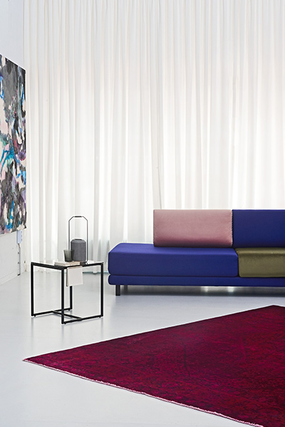 TYME sofa in blue with one cushion in pink velvet and one in olivegreen velvet, SYDE coffee table with black frame and glass tabletop