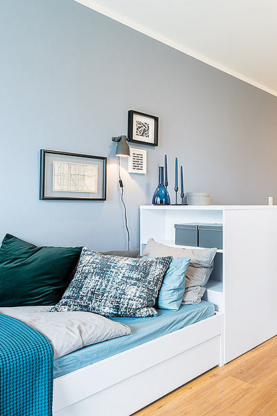 Bed in white with a functional headboard consisting of two large shelves on the front and the back