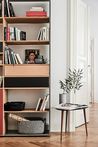 Shelf in a combination of oak, red, black and grey, coffee table with legs in walnut and a black tabletop