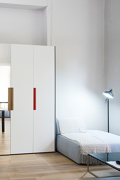 Wardrobe with two white and a mirrored door, gray side walls, two handles in oak and one in red